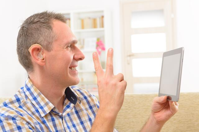 Deaf man using sign language on the tablet.jpeg