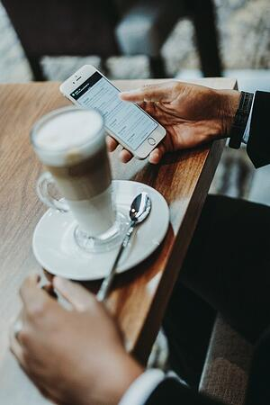 checking email on a phone with coffee - how to create emails that convert
